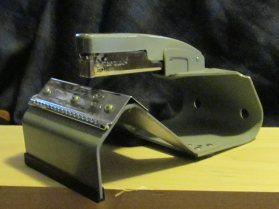 This is the key tool. If you invest in a saddle stapler, you're investing in making minicomics. It's easy to see how it works: fold your pages and assemble your comic, then arrange it over the saddle. The framework assures that the staple goes right into the center of the spine, every time.